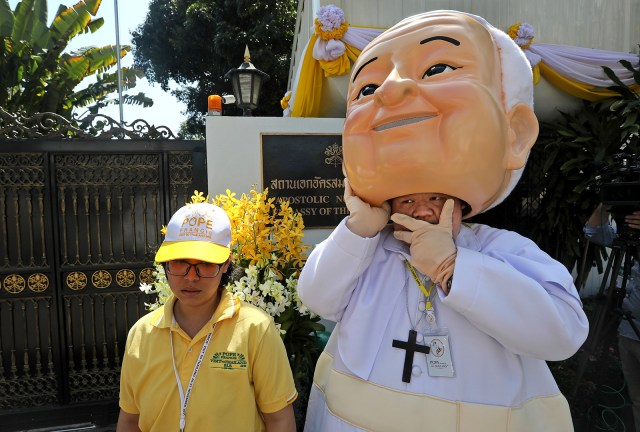 A man lifts a giant mask of Pope Francis off his head as he waits outside the Apostolic Nunciature Embassy of the Holy See in Bangkok on Nov. 20, 2019. Pope Francis toured Thailand and Japan on a trip, part of a mission to boost the morale of those countries' tiny minority Catholic communities. (AP Photo/Manish Swarup)