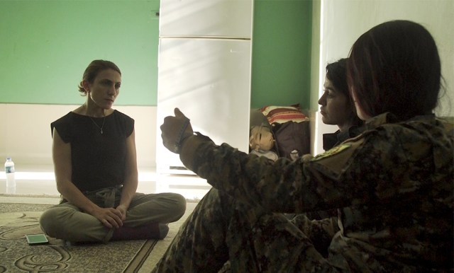 "Author Gayle Tzemach Lemmon, left, interviews a group of women fighters during the fight for Raqqa in the summer of 2017. Photo courtesy of ""The Daughters of Kobani"""