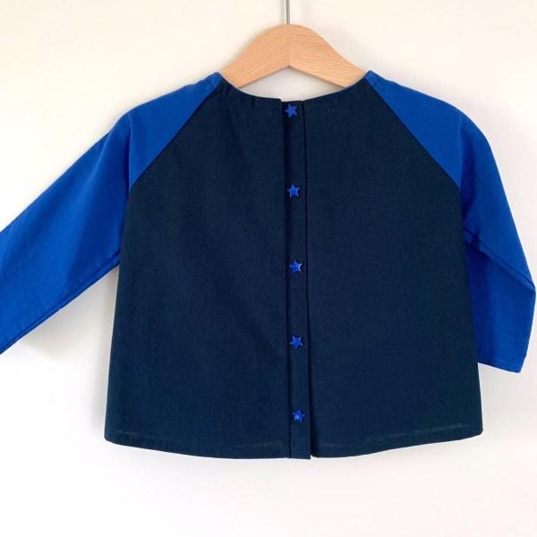 Dos d'une blouse pour garçon sur un cintre