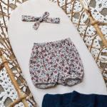 Bloomer bébé et son bandeau assorti dans un berceau