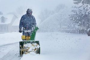Man cleaning snow with a snow blower.