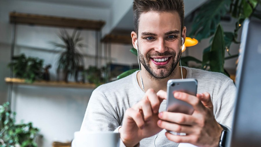 Portrait of smiling man with earphones sitting at coffee shop and using mobile phone