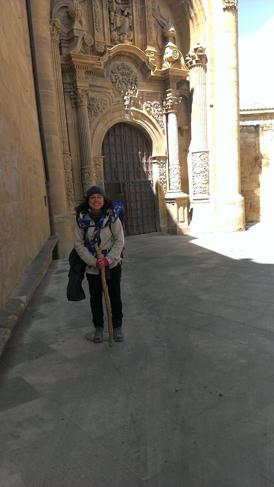Iza in hiking gear in front of the ornate carved sandstone facade of a building