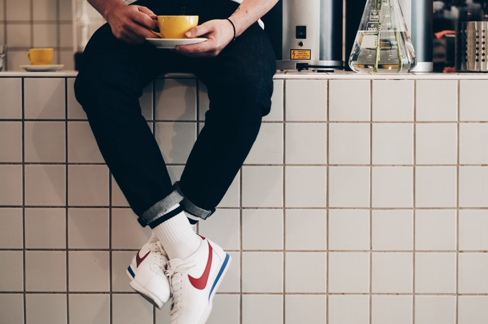 Man drinking coffee wearing Nike Cortez - Extra 20% Off Sale Banner