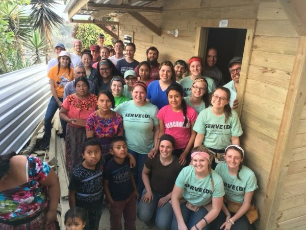 San Raymundo residents stand outside their newly constructed home along with Casas por Cristo workers and volunteers who helped build the house.