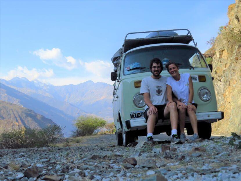 Pareja senta en Kombi con paisajes de montañas
