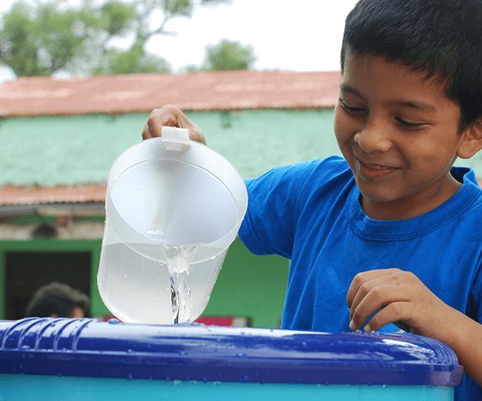 Niño sirviendo agua