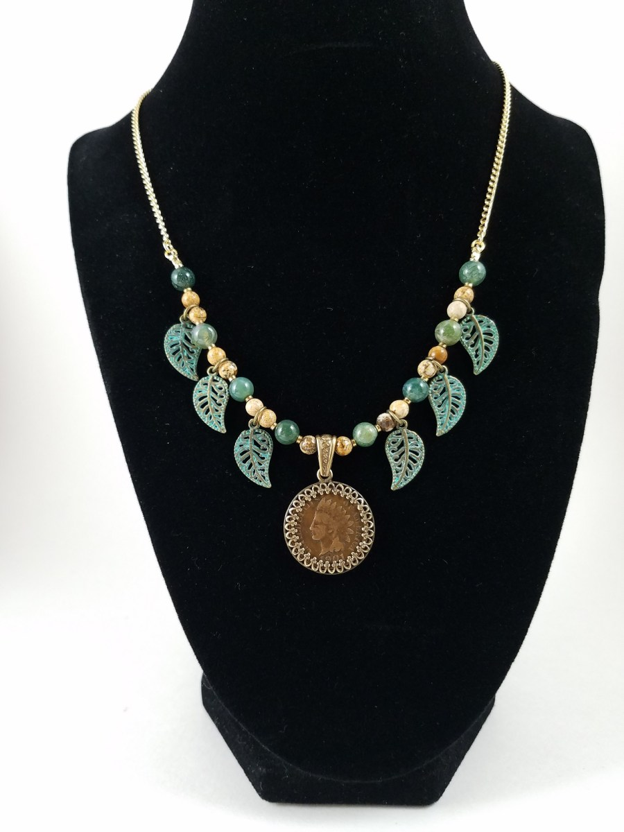 Necklance with American Indian head penny, brown and green beads, and verdigris leaves.