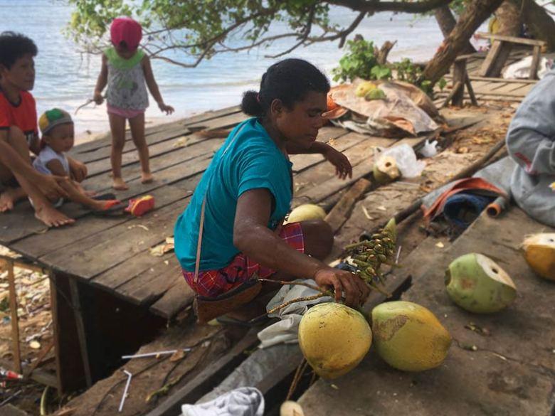 Travelling Women cutting coconuts in Berlin Wall, Sorong