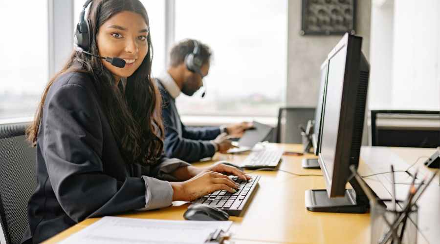 a smiling woman working in a call center while looking at camera