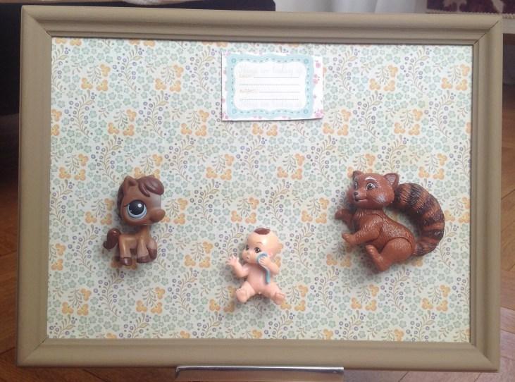 Cadre de naissance Bebe garçon . 2 figurines marron ( un écureuil et un petshop ) entourent un petit bebe .