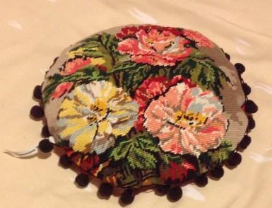 Petit coussin rond fleuri à pompons , arrière rose vif .Diametre : 30 cm environ ( 25 €)