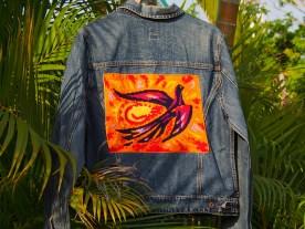 Un canevas aux couleurs vives typiques des années 70 au dos de ce blouson en jean . Taille L .