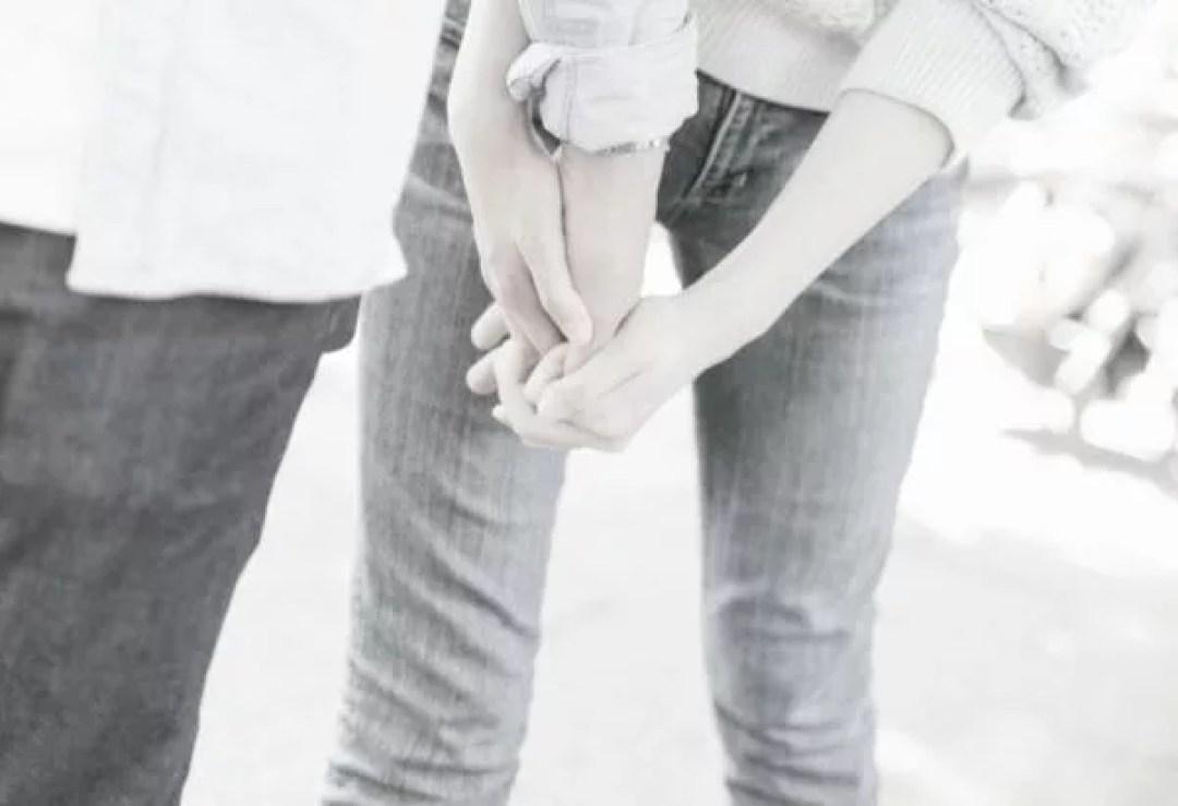 彼の手を両手で握る彼女の手 恋人つなぎ カップル