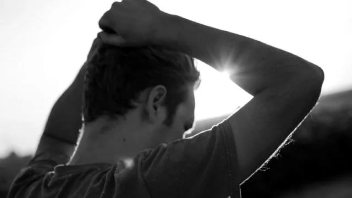 頭を抱える男性 夕日