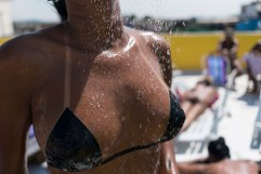 In this Jan. 15, 2017 photo, a woman showers after removing part of her bikini made out of electrical tape on the rooftop of the Erika Bronze salon in the suburb of Realengo in Rio de Janeiro, Brazil. While women in some European countries sunbathe topless to avoid tan lines, in Rio these women pay up to US$20 (70 Brazilian reais) a session to get sharp ones that contrast with their gleaming golden brown skin. (AP Photo/Renata Brito)