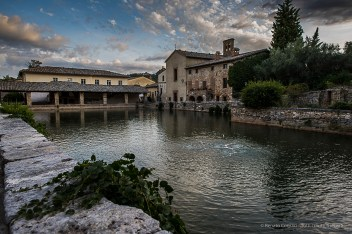 Bagno a Vignoni, the hot pool in Piazza del Moretto, with a caper plant in the foreground. Nikon D810, 24mm (24.0mm ƒ/1.4) 1/320 ƒ/4.5 ISO 400