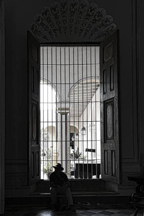 A man in a hat silhouetted against window in Cuba.