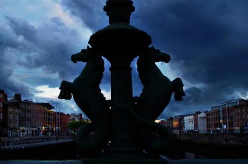 The Grattan Bridge silhouetted against a sunset in Dublin, Ireland.