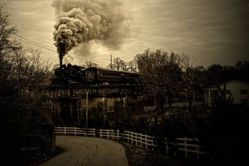 Steam blowing up into a cloudy sky as the engine crosses the trestle.