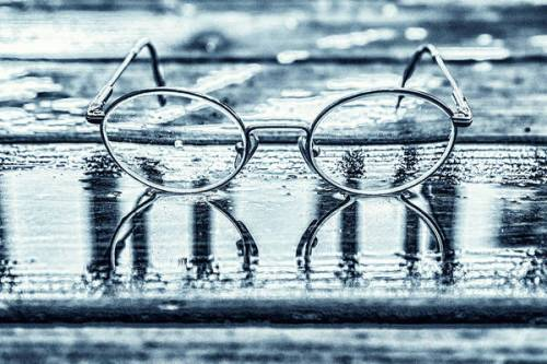 Eyeglasses reflected in water puddle
