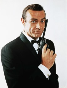 ca. 1968 --- Waist-up portrait of Sean Connery, as James Bond, caressing the barrel of a gun against the side of his face. Connery is wearing a tuxedo and bow tie and smiling slightly. --- Image by © Bettmann/CORBIS