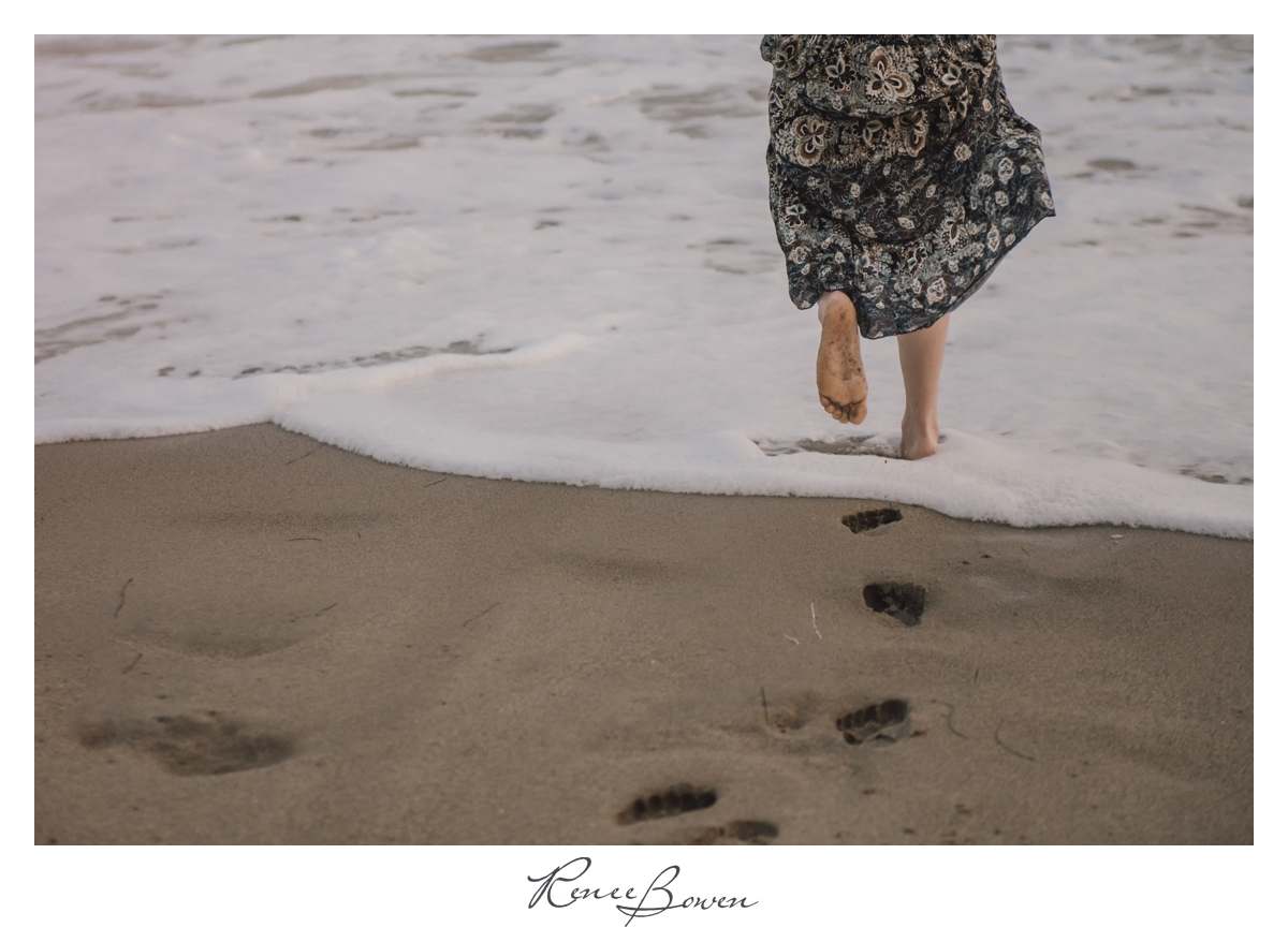 girl in floral dress senior pics feet in sand and water