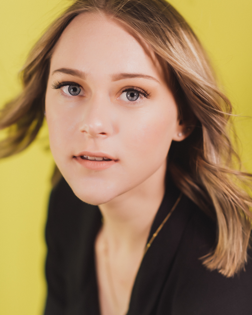 blond girl on yellow background senior portraits