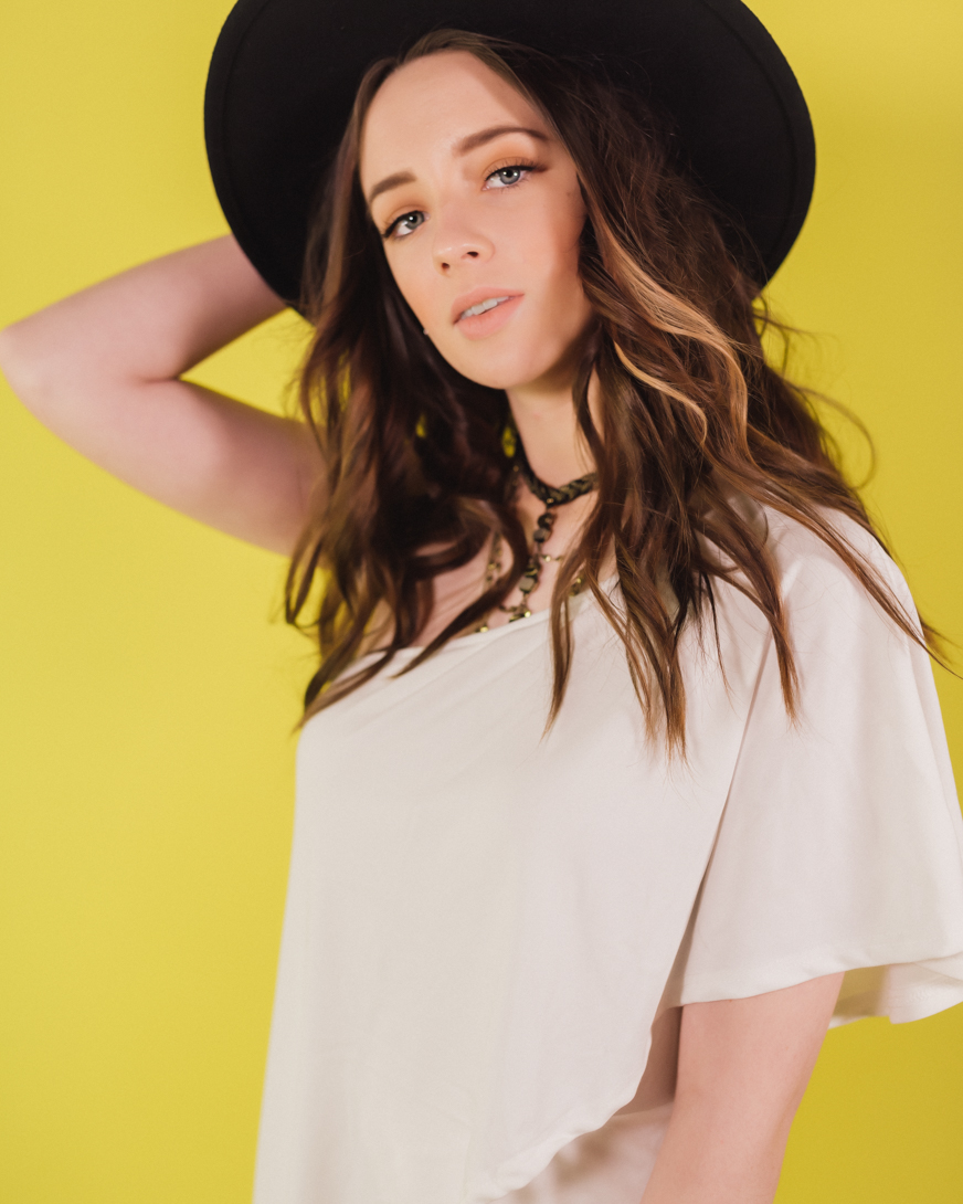 girl in black hat on yellow backdrop senior photosession