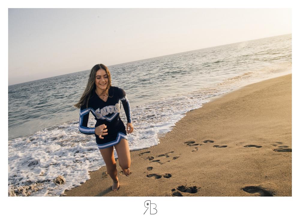 senior girl in cheerleading outfit running on the beach backlit renee bowen seniors