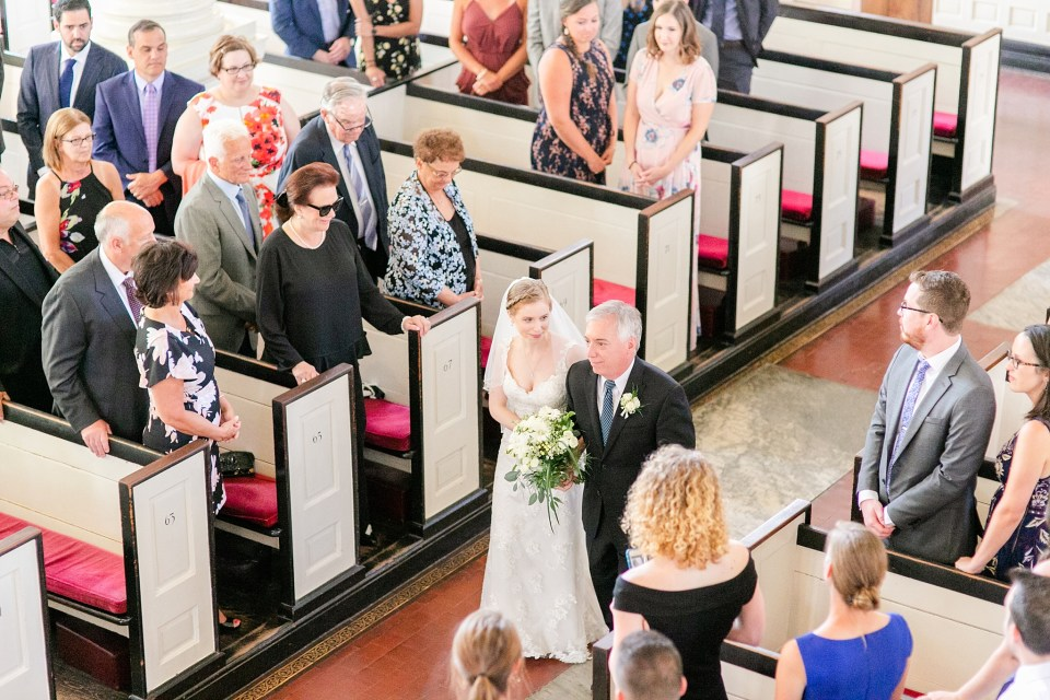 bride walks down aisle with father photographed by Renee Nicolo Photography