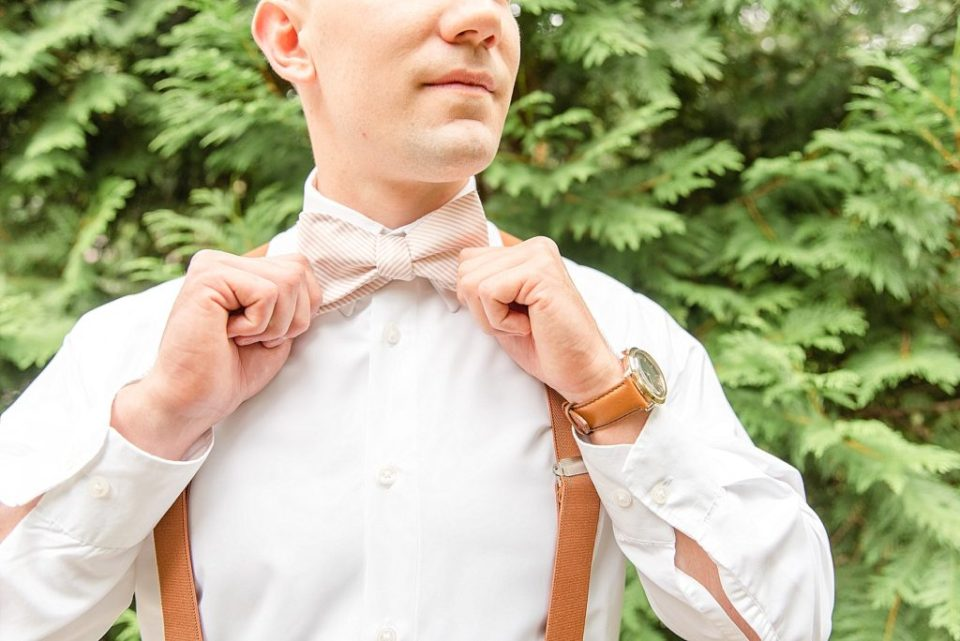 groom adjusts tie for wedding day with Renee Nicolo Photography
