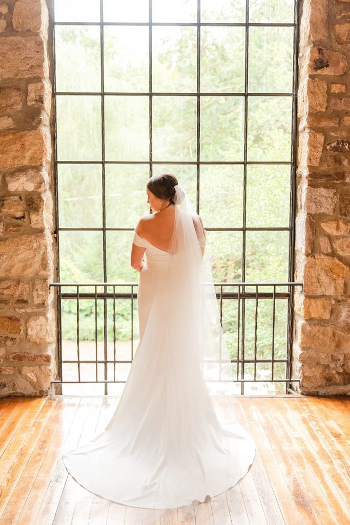 bride poses by window on wedding day photographed by Renee Nicolo Photography