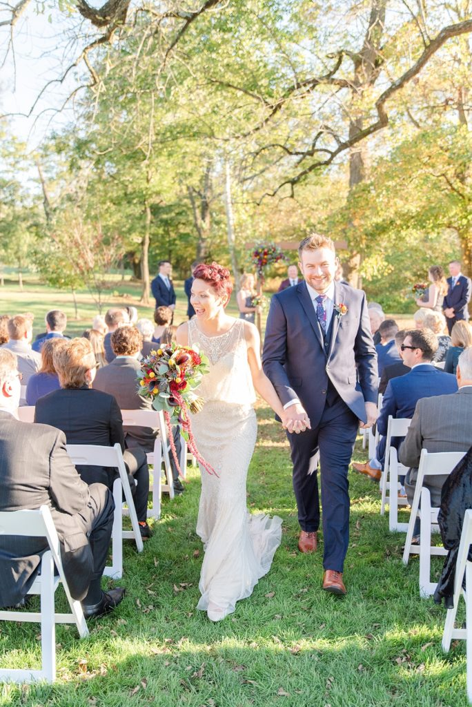 joyful newlyweds walk up aisle photographed by Renee Nicolo Photography