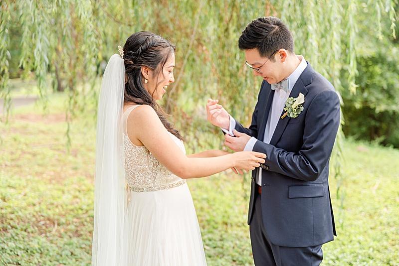 bride helps groom adjust suit during first look