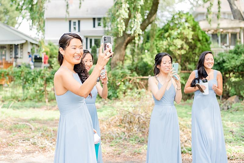 bridesmaids snap photos during first look before NJ backyard wedding