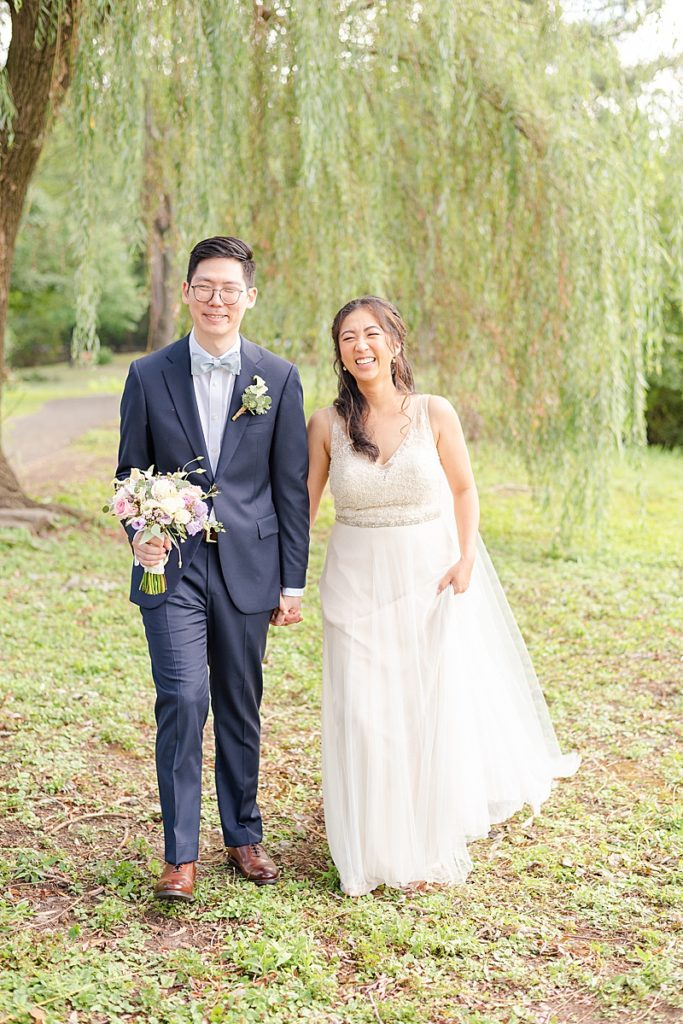 bride and groom hold hands walking under willow tree