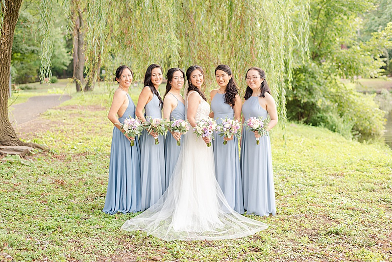 bride and bridesmaids pose under willow tree at Cooper Pond Park