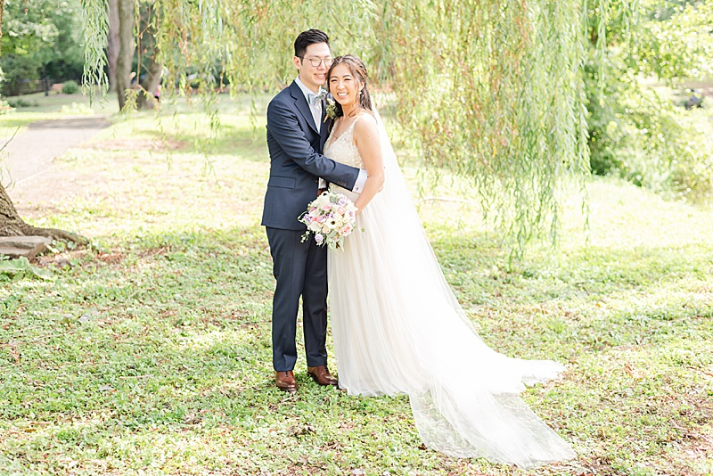 bride and groom stand under willow tree at Cooper Pond Park