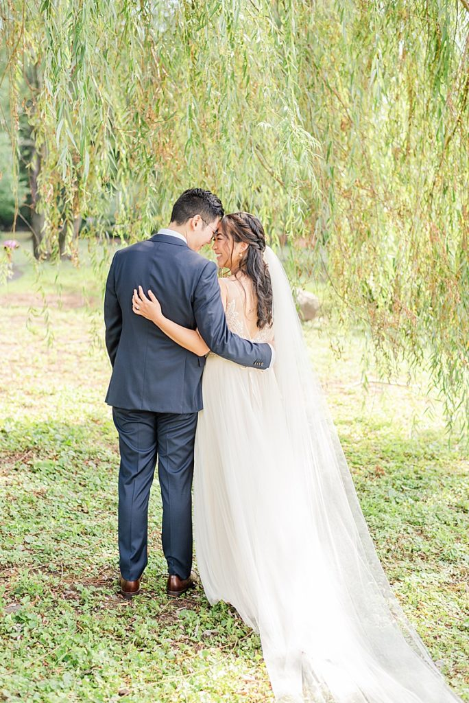 bride and groom stand touching foreheads under willow tree in New Jersey