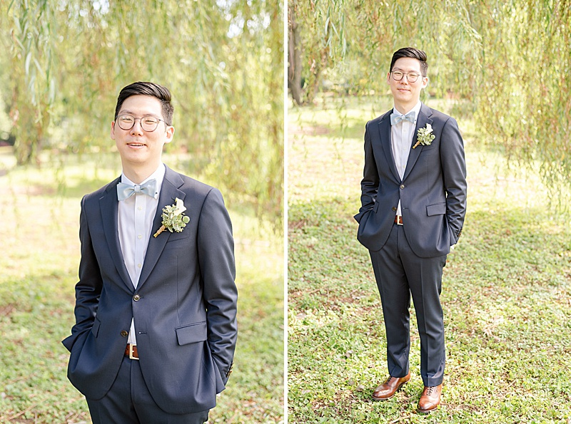 groom poses in suit with brown shoes under willow tree