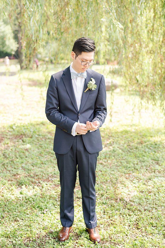 groom adjusts suit before NJ backyard wedding