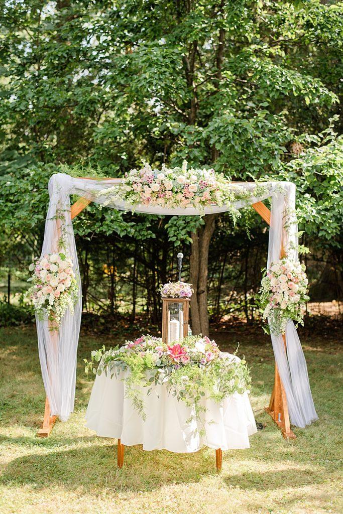 unity candle sits under arbor for NJ backyard wedding ceremony