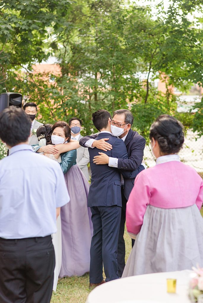 groom hugs father during wedding ceremony