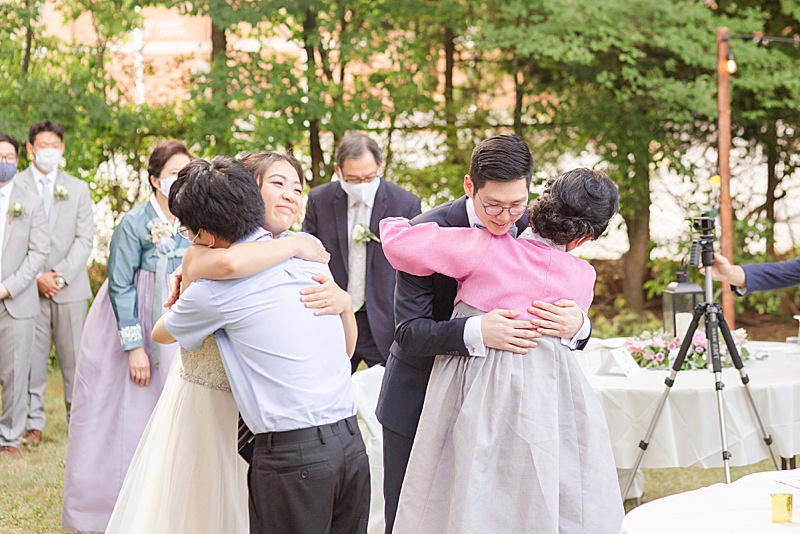 bride and groom hug mother and brother
