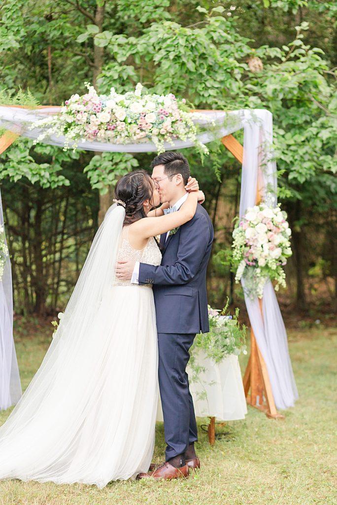 bride and groom kiss during NJ backyard wedding ceremony
