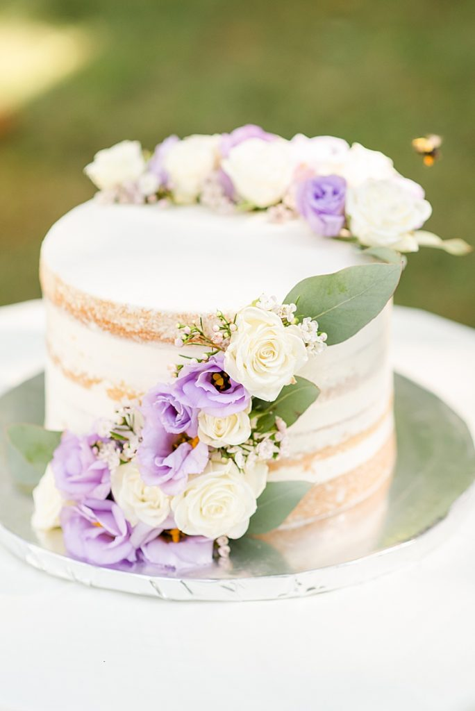 naked cake with purple and white flowers