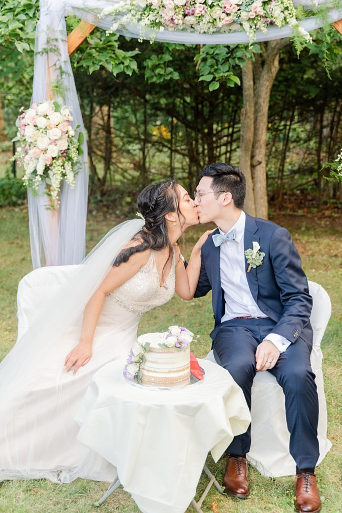 bride and groom kiss after cutting cake