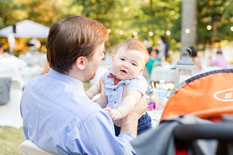 baby and dad play during backyard reception