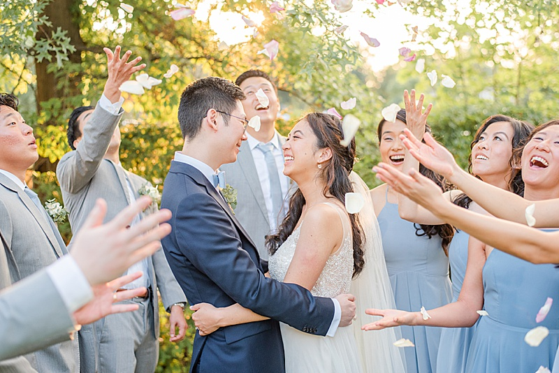 newlyweds pose while flower petals fall